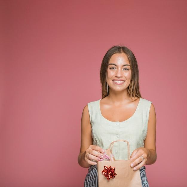 Mujer sonriente que sostiene la caja de regalo del panier contra el contexto coloreado