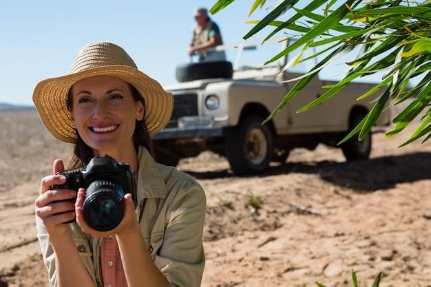 Mujer sonriente que sostiene la cámara con el hombre en el vehículo todoterreno