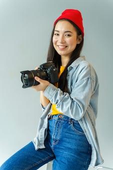 Mujer sonriente que sostiene la cámara profesional