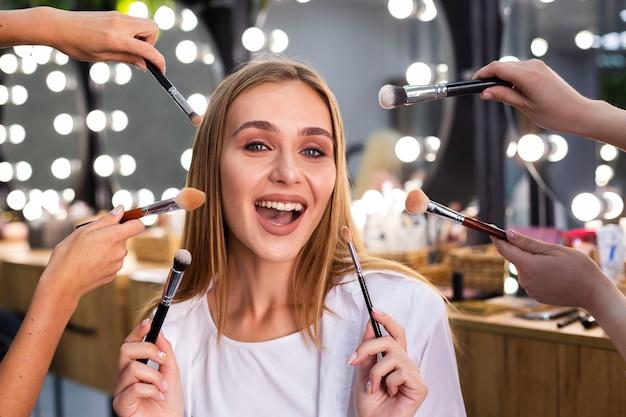 Mujer sonriente que sostiene cepillos del maquillaje