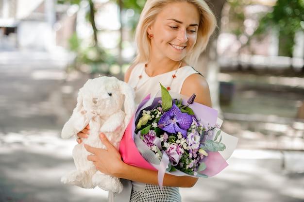 Mujer sonriente que sostiene una composición de flores y juguete