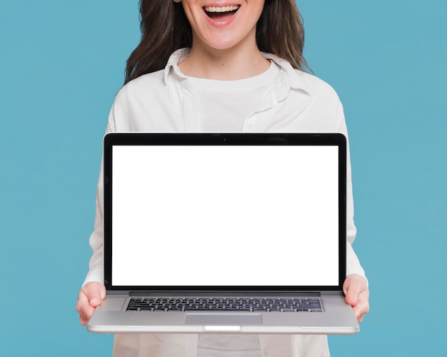 Mujer sonriente que sostiene una computadora portátil