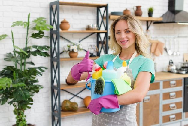 Mujer sonriente que sostiene el cubo de los productos de limpieza que muestran el gesto del thumbup que se coloca en casa