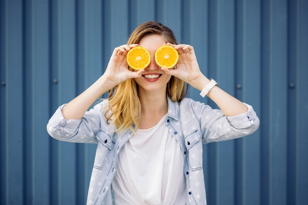 Mujer sonriente que sostiene dos naranjas en manos
