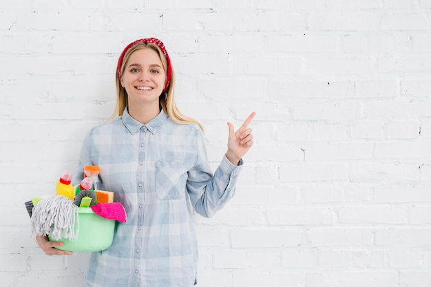 Mujer sonriente que sostiene el equipo de limpieza
