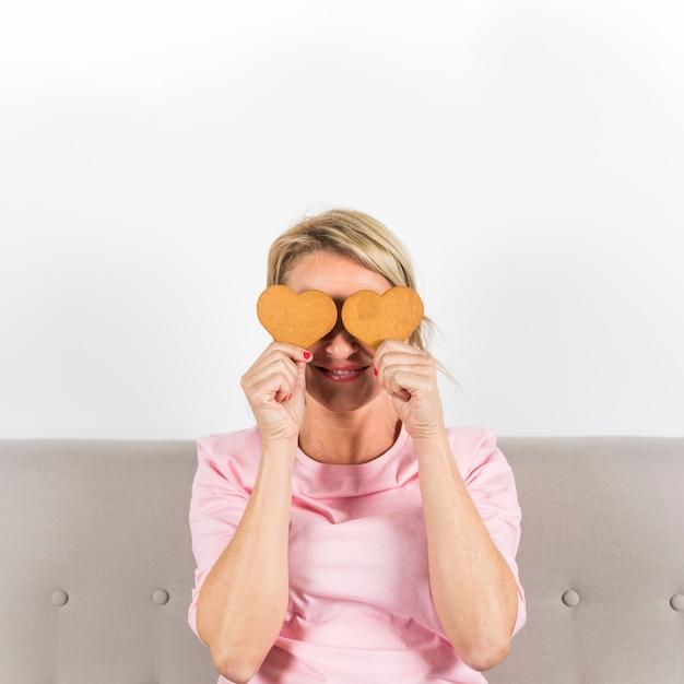 Mujer sonriente que sostiene las galletas de la forma del corazón delante de sus ojos contra el contexto blanco