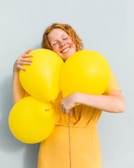 Mujer sonriente que sostiene los globos