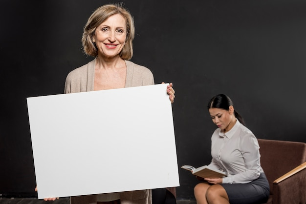 Mujer sonriente que sostiene la hoja de papel en blanco