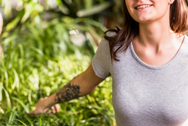 Mujer sonriente que sostiene las hojas verdes de plantas