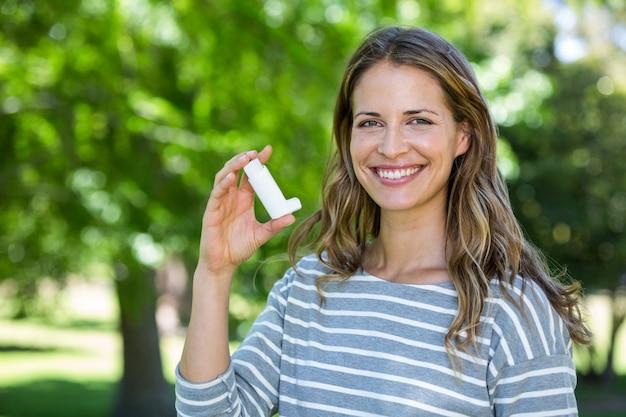 Mujer sonriente que sostiene el inhalador del asma