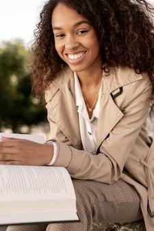 Mujer sonriente que sostiene un libro abierto afuera