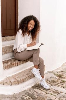 Mujer sonriente que sostiene un libro abierto