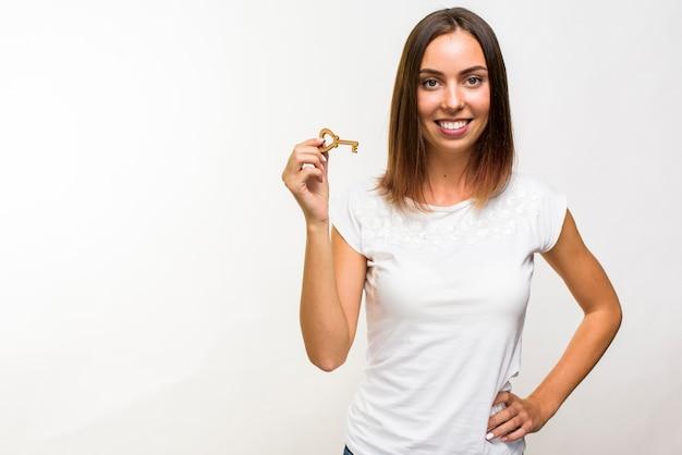 Mujer sonriente que sostiene una llave con copyspace