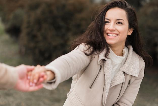 Mujer sonriente que sostiene la mano del hombre afuera