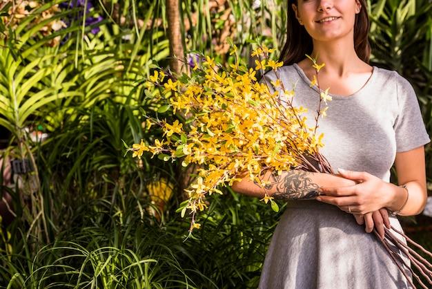 Mujer sonriente que sostiene el manojo de ramitas de la planta