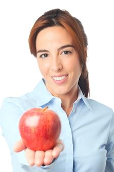 Mujer sonriente que sostiene una manzana roja