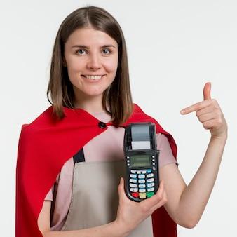 Mujer sonriente que sostiene la máquina pos