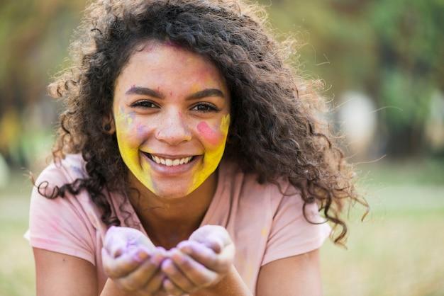 Mujer sonriente que sostiene la pintura en polvo en sus manos