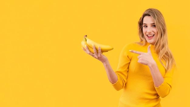Mujer sonriente que sostiene plátanos