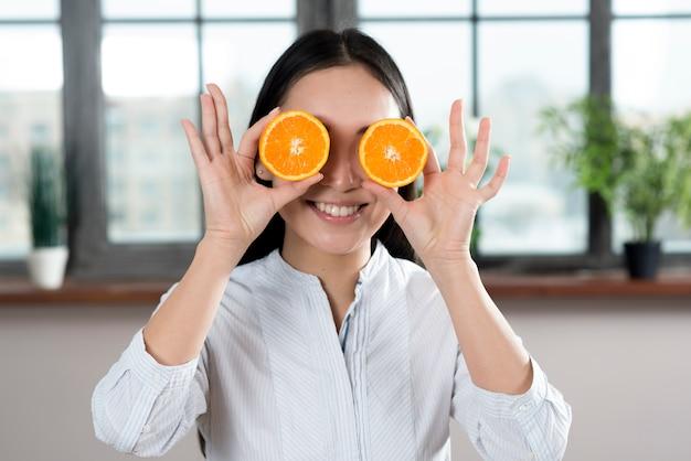 Mujer sonriente que sostiene rebanadas de naranja delante de sus ojos en casa