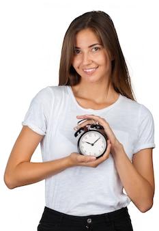 Mujer sonriente que sostiene el reloj de alarma