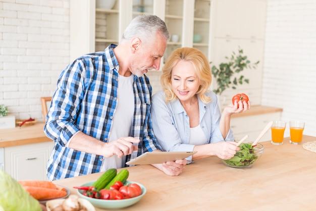 Mujer sonriente que sostiene el tomate en la mano que mira el control digital de la tableta de su marido
