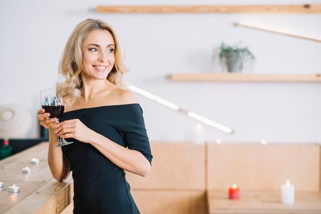 Mujer sonriente que sostiene el vino de cristal