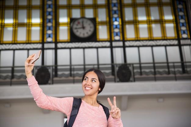 Mujer sonriente que toma la foto del selfie y que muestra la muestra de la victoria