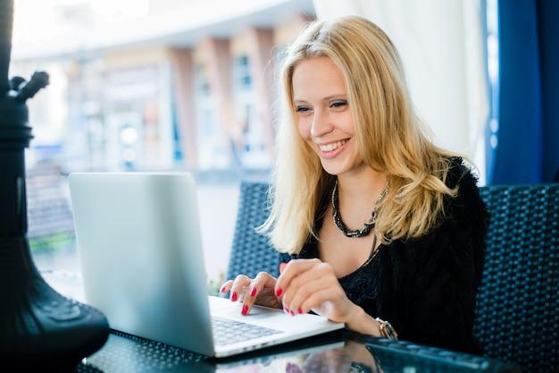 Mujer sonriente que trabaja con la computadora portátil al aire libre en el café