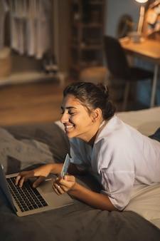 Mujer sonriente que trabaja en la computadora portátil de casa