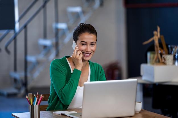 Mujer sonriente que trabaja en el escritorio y que tiene una llamada telefónica