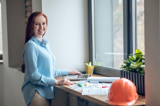 Mujer sonriente que trabaja con esquemas en el alféizar de la ventana