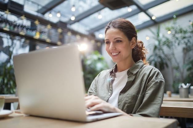Mujer sonriente que usa la computadora portátil en café