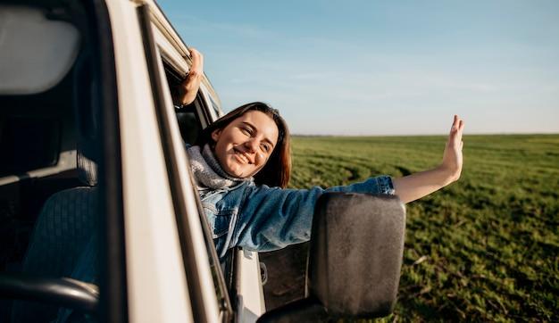 Mujer sonriente quedarse con la cabeza fuera de una camioneta