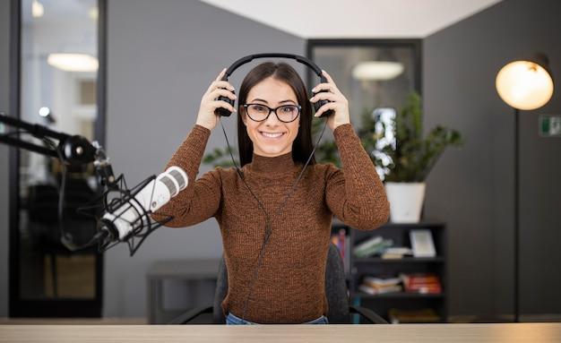 Mujer sonriente en la radio con micrófono y auriculares