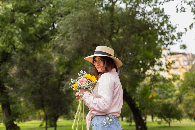 Mujer sonriente con ramo de flores en el parque