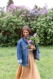 Mujer sonriente con ramo lila