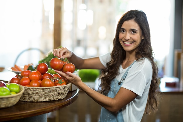 Mujer sonriente recogiendo tomates frescos de la canasta