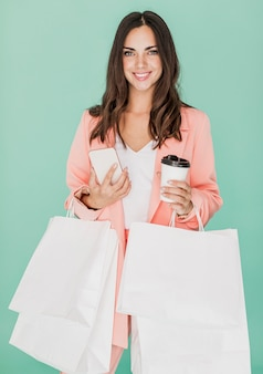 Mujer sonriente con redes de compras y teléfono inteligente