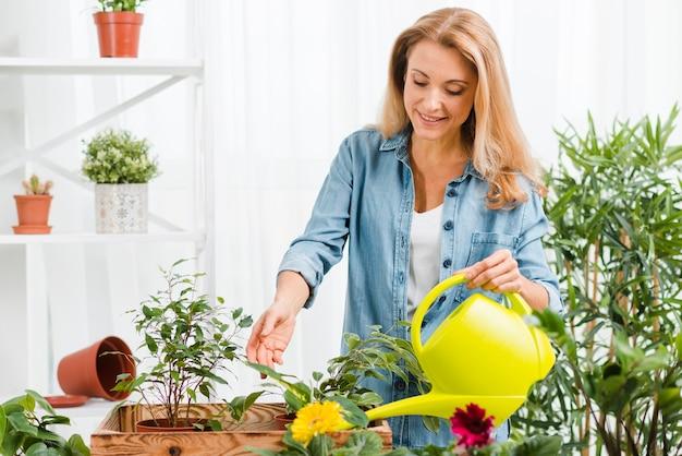 Mujer sonriente regando flores