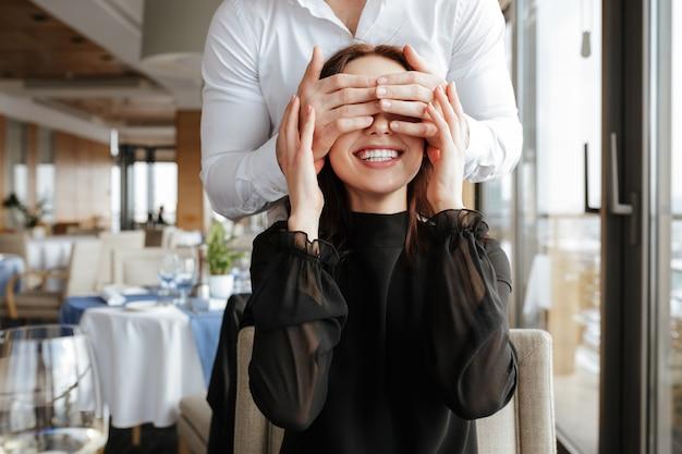 Mujer sonriente en restaurante con hombre detrás de ella