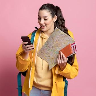 Mujer sonriente revisando su teléfono mientras sostiene un mapa y su pasaporte