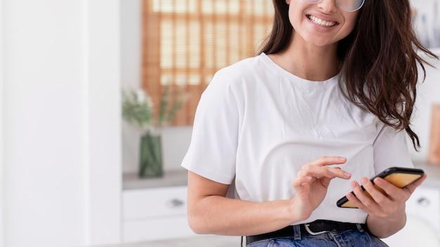 Mujer sonriente revisando su teléfono