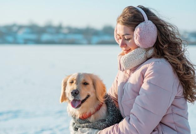 Mujer sonriente con rizos largos abraza a su perro golden retriever