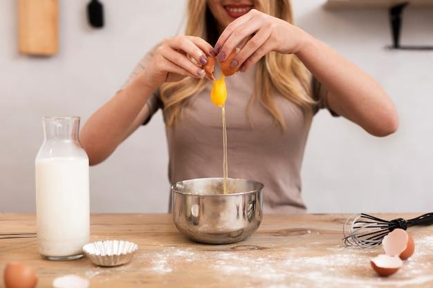 Mujer sonriente rompiendo el huevo en un recipiente metálico