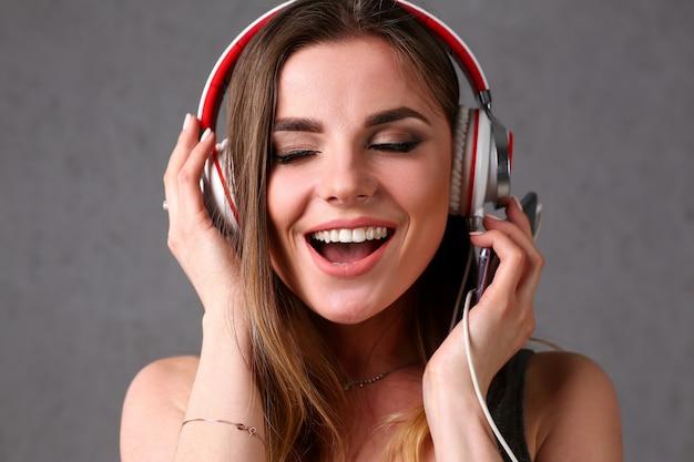 La mujer sonriente rubia hermosa con los ojos cerró el uso de los auriculares que escuchaban la música preferida en fondo gris. radio de audiolibros de la vida urbana moderna que tiene momentos con el concepto de movimiento de baile