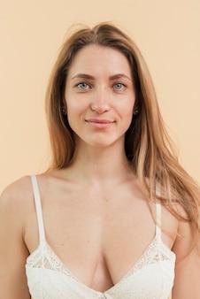 Mujer sonriente rubia joven en sujetador