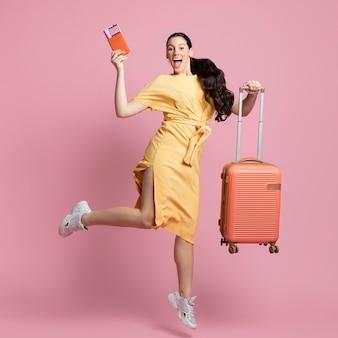 Mujer sonriente saltando mientras sostiene su equipaje y pasaporte