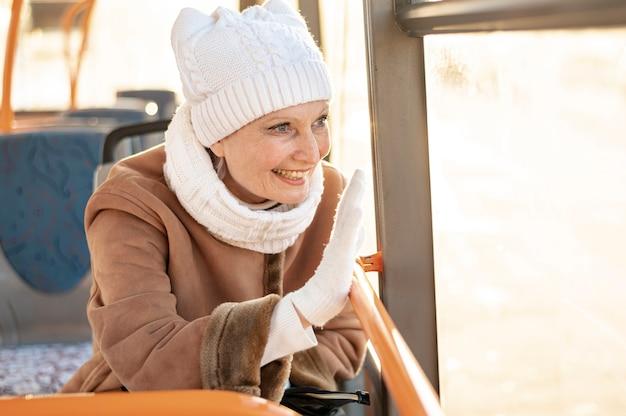 Mujer sonriente saludando desde el autobús