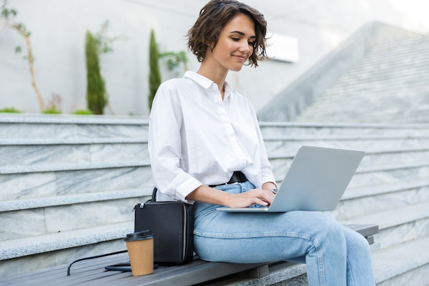 Mujer sonriente sentada en un banco al aire libre